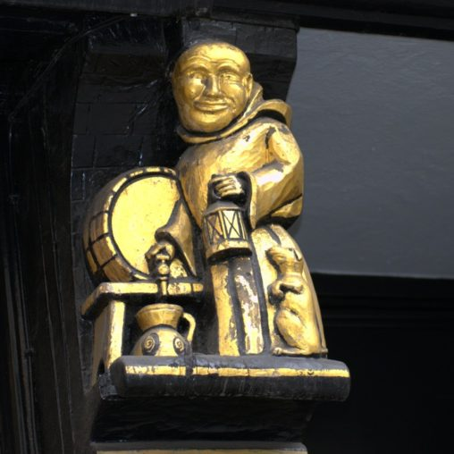 Carved figure of a monk pouring beer from a barrel.